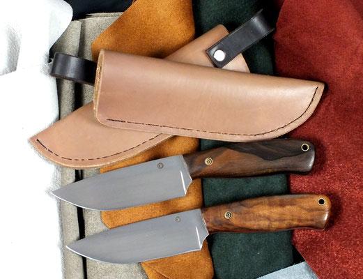 Zwei große Outdoor-Messer aus Kohlenstoffstahl und heißgewachsten Lederscheiden. Die Griffe sind mit Ziricote und türkischem Nussbaum.