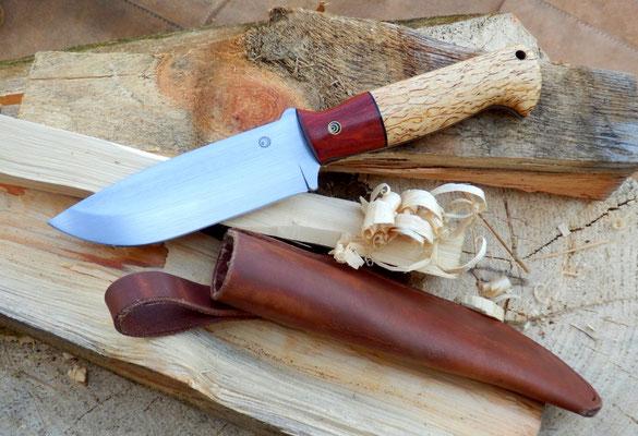 Ein massives Outdoor Messer genau nach Kundenwunsch! Aus Kugellagerstahl, einem Griff aus Redwood und karelischer Maserbirke und einer heißgewachsen Lederscheide.