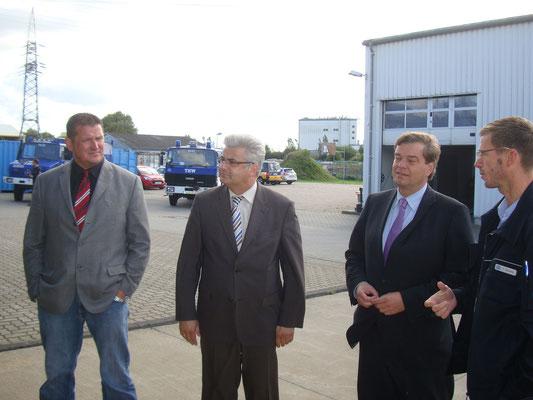 von rechts: Torsten Döscher (THW), PSts Enak Ferlemann, Axel Knoerig MdB, u. Thomas Brunken (Ortsbürgermeister Lüdingworth) bei der Besichtigung des THW in Cuxhaven