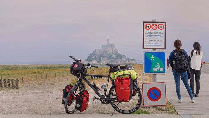 Rad und zwei Touristen vor Mont St. Michel Frankreich