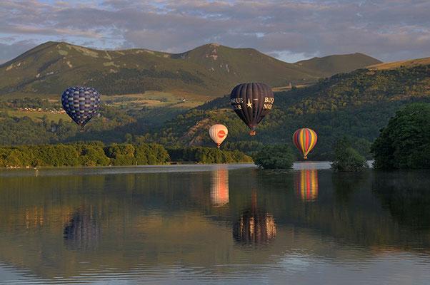 vier Heißluftballons in Murol Frankreich Spiegelung im See
