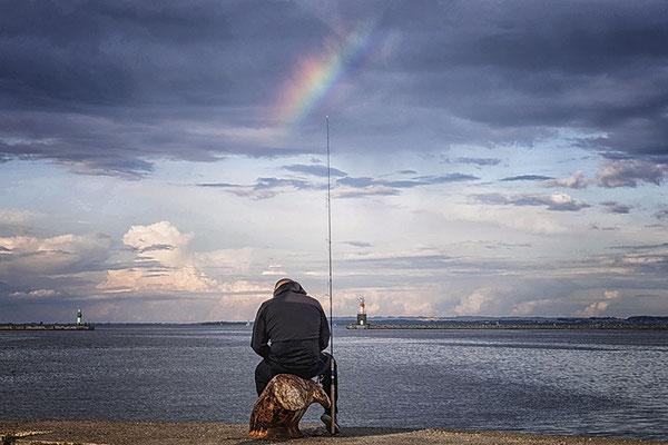 Angler am Ufer mit Regenbogen