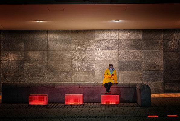 Frau mit gelber Jacke bei rotem Licht
