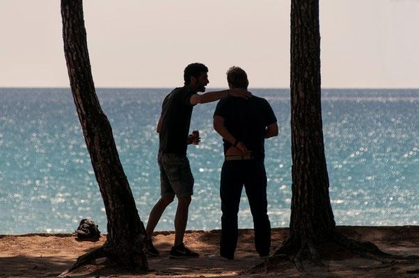 zwei Männer im Gegenlicht und Palmen mit Blick auf Meer Lanzarote Spanien
