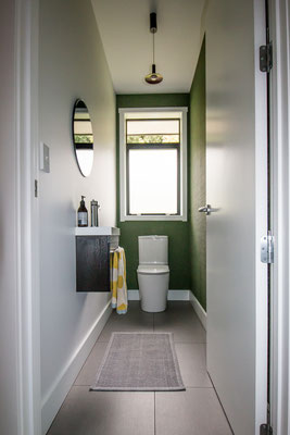 Two walls is often all you need for wallpaper in a toilet - this one a fabulous textural green vinyl.