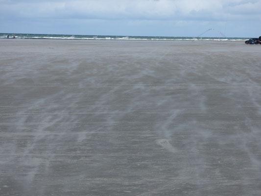 So sah es meist die ersten Tage am Strand aus. Der kräftige Wind treibt den Sand über den Strand. Sandpeeling gratis.