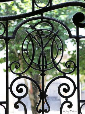 Détail de la porte d'entrée en fonte ouvragée et aux initiales du Médicis Palace à La Bourboule - Auvergne - France