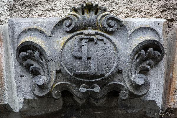 Détail des initiales du fronton de la porte d'entrée sculpté dans de la pierre de lave de l'ancien Médicis Palace à La Bourboule - Auvergne - France