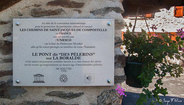 """Plaque sur le pont dit """"des pèlerins"""" sur La Boralde à Saint-Chély-d'Aubrac indiquant l'inscription sur la liste du Patrimoine Mondial de L'UNESCO les Chemins de Compostelle - France - (santiago de compostela) - Via Podiensis"""