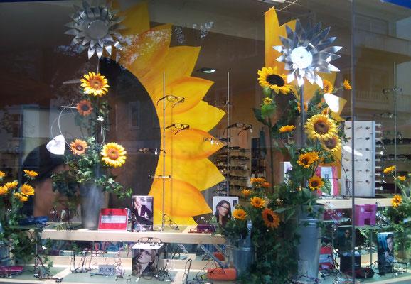 Schaufensterdekoration mit Sonnenblumen aus Metall und Holz