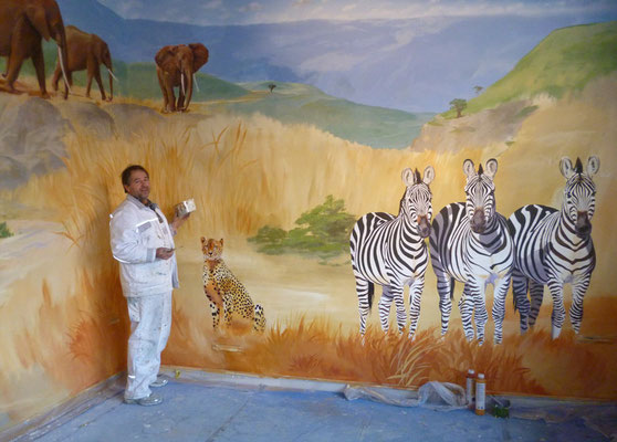 Arbeitssituation während der Wandmalerei der afrikanischen Steppe mit Zebras und Elefanten.