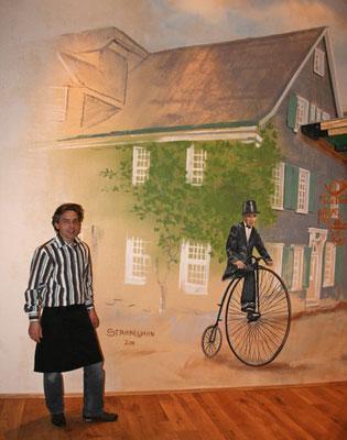 Das Bild eines Fahrers auf dem Hochrad mit einer realen Person im Vordergrund.