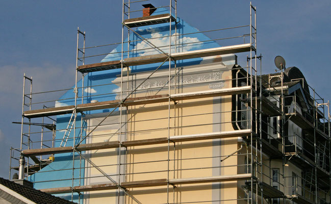 Scheinarchitektur Malerei an einer Fassade im halbfertigen Zustand. Der Himmel und einzelne Stuckelemente sind bereits fertiggestellt.