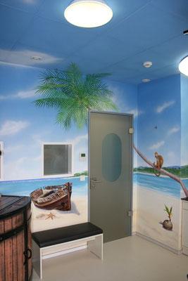 Der Eingangsbereich des Piratenzimmers in der Arztpraxis. Ein gestrandetes Boot liegt am Strand.