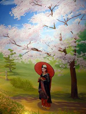 Geisha beim Spaziergang im Schatten des in voller Blüte stehenden Kirschbaumes.