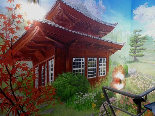 Schließlich ereicht er das Teehaus inmitten der Blütenpracht der japanischen Landschaft.
