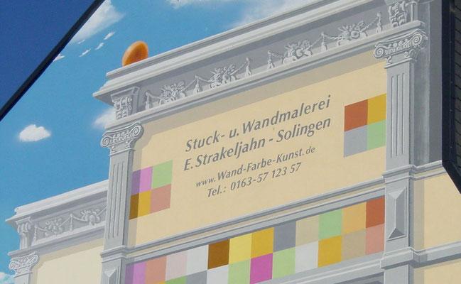 An der künstlerisch gestalteten Fassade wurde in die Malerei der Scheinarchitektur noch Werbung in eigener Sache aufgebracht.