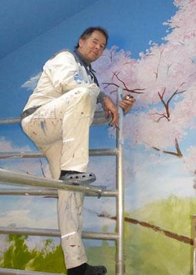 Arbeit in luftiger Höhe an der Baumkrone des blühenden Kirschbaums.