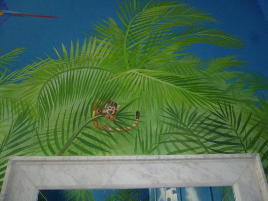 Detailansicht eines Halbaffen zwischen den Palmwedeln.