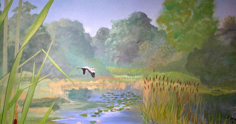 Im Abenddunst zieht ein Reiher seine Bahn über den See.