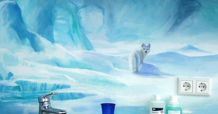 Ein Polarfuchs, oder auch Eisfuchs genannt, blickt noch einmal zurück bevor er in der Landschaft mit Höhle verschwindet.