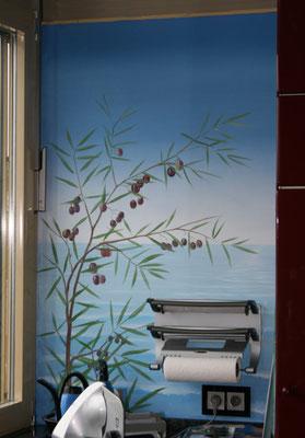 Ein Olivenbaum vorm weiten Meer ziert diese Küchenwand.