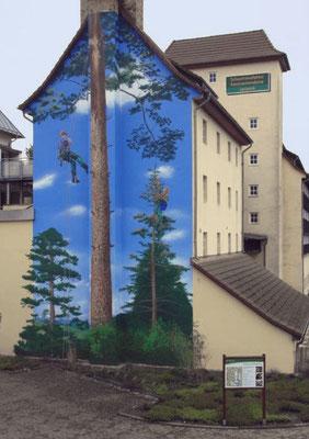 Die Fassadenmalerei mit dem Landschaftsbild. Blauer Himmel, Wald, Landschaft und die Arbeiter bilden ein harmonisches Ganzes
