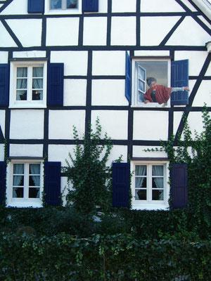 An einem bergischem Fachwerkhaus wurde das zugemauerte Fenster durch eine Illusionsmalerei wieder geöffnet.
