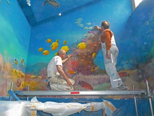 Momentaufnahme während einer Wandmalerei. Die Komplettbemalung eines Bades mit dem Thema der karibischen Meereswelt