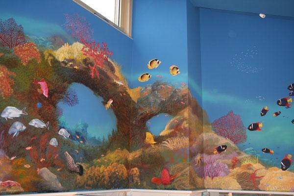 Ein großes Korallenriff mit Fächerkorallen wird von tropischen Fischen bevölkert: Muränen, Juwelenbarsch, Snapper und vielen anderen farbenfrohen Bewohnern
