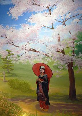 Eine Geisha im traditionellen Gewand, dem Kimono, beim Spaziergang im Schatten des in voller Blüte stehenden Kirschbaums.