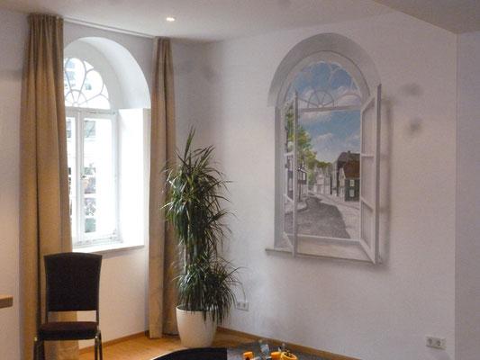 Die Illusionsmalerei im Tagungsraum täuscht den Blick durch das offene Fenster auf den Ort vor.