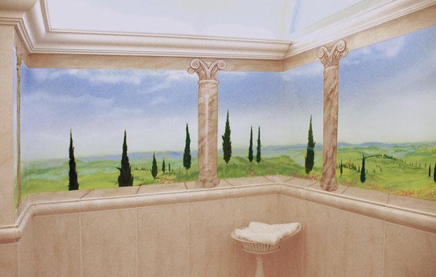 Wandbemalung in einem Badezimmer mit Blick in die Toskana und als Illusionsmalerei ausgeführten Säulen und Stuckelementen.