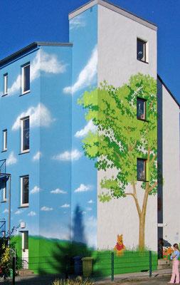 Traditionelle Fassadenmalerei einer Kindertagesstätte. Die Giebelwand ziert ein Baum und die Rückwand ein Wolkenhimmel.