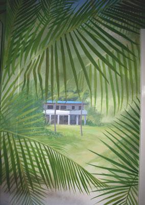 Durch die Palmwedel dieser Detailansicht blickt man auf die Safari-Lodge.