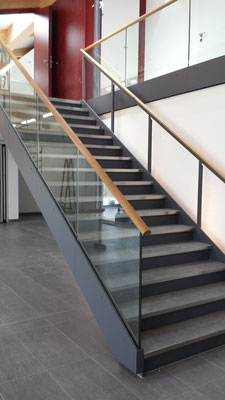 Treppe mit Blechstufen. Belag Fliesen, Ganzglasgeländer