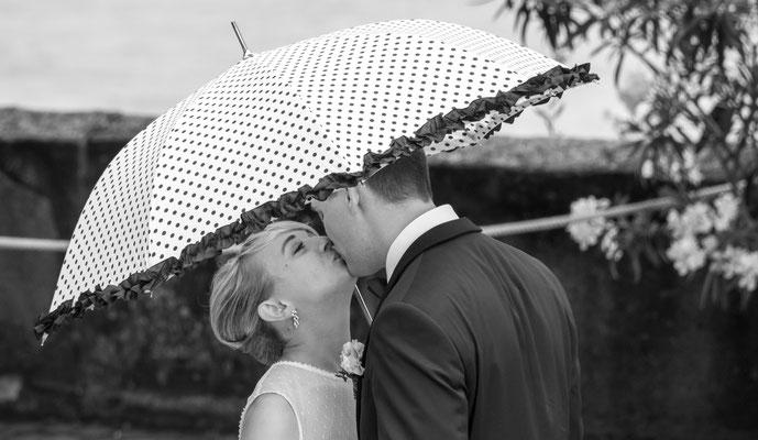 Hochzeitskuss unter Regenschirm