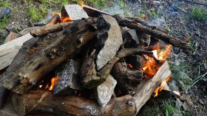 die Steine mit Wünschen Großvater Feuer übergeben