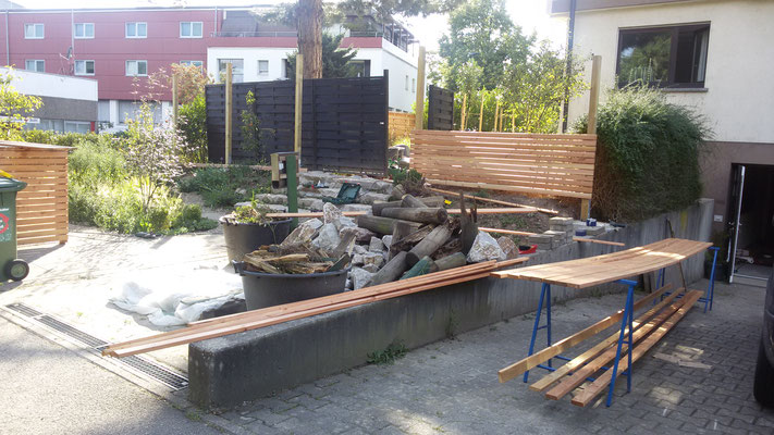 Der Zaun wird gebaut, erst die Hecke gerodet, die Fundamente gebaut, Pfosten gesetzt, Holzlasur auf jedes Brett ...