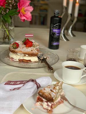 Baltā galdauta kafejas galds ar rabarberu kūku pie Leukefeldu ģimenes