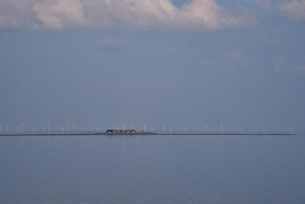 Blick auf Hallig Gröde. Im Hintergrund ein Windpark auf dem Festland.