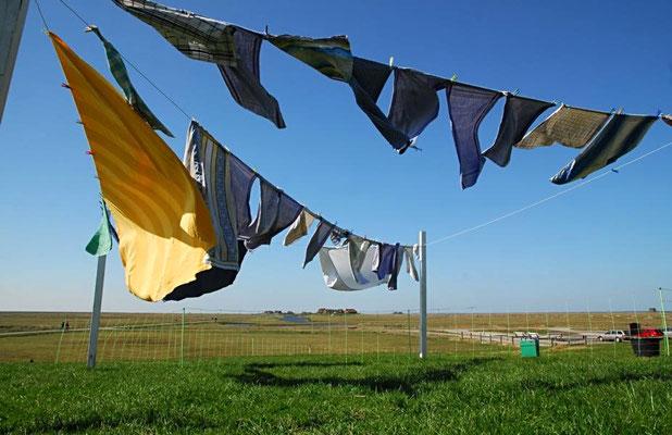 Große Wäsche auf der Hanswarft. Eine Warft ist ein aus Erde aufgeschütteter Siedlungshügel, der dem Schutz von Menschen und Tieren bei Sturmfluten dient.