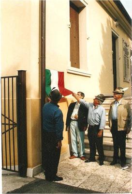 Il capogruppo ERNESTO ALLEGRINI, scopre l'insegna della nuova sede, prima dell'apertura ufficiale. Sono presenti il consigliere sezionale Mino Basaglia, il sindaco Pietro Meschi e S.E. il Gen. Giorgio Donati