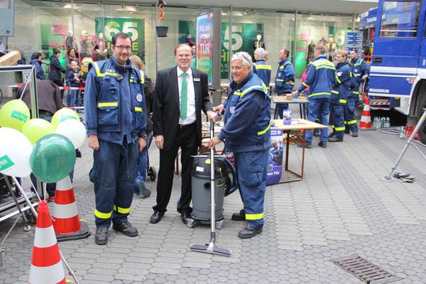 Walter Enders, Geschäftsführer von Galeria Kaufhof übergibt den Wassersauger an Ortsbeauftragten Peter Brandmann und 2. Vorsitzenden des Fördervereins Stefan Mühlmann