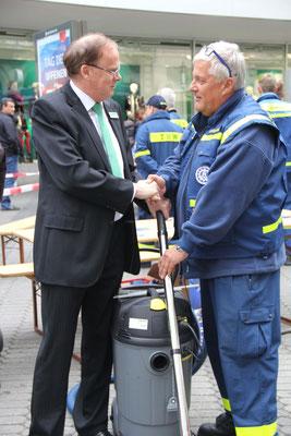 Walter Enders, Geschäftsführer von Galeria Kaufhof übergibt den Wassersauger an Ortsbeauftragten Peter Brandmann