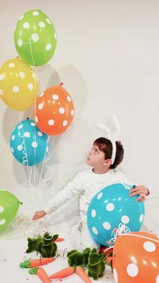 bambino vestito da coniglio di pasqua con palloncini colorati e coniglietti