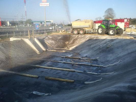 Beschweren mittels Sandsäcken, Bewässern mit Wassertank und Traktor