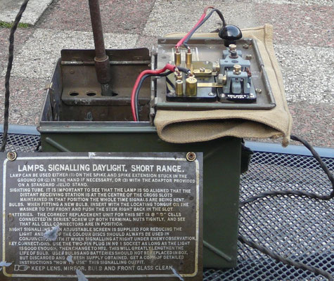 Morse signalling lamp with a very narrow beam and a Morse key unit which can be mounted on a staked in the ground provided in the carrying case.