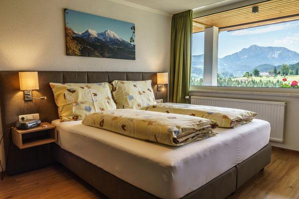 Fewo B - Schlafzimmer mit Doppelboxspringbett und Balkon mit herrlicher Aussicht