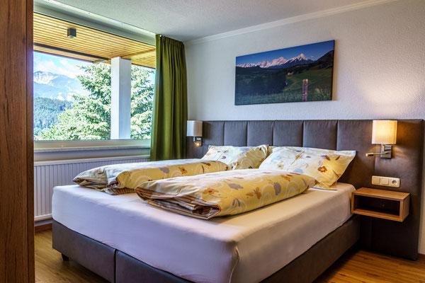 Fewo D - Schlafzimmer 1 mit Doppelboxpringbett und Couch